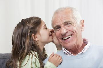 Mädchen flüstert in Großvaters Ohr