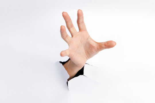 Female hand reaching through torn paper sheet