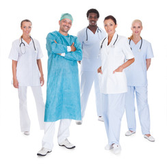 Happy Doctor In Surgical Gown With His Coworkers