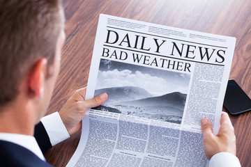 Close-up Of Businessman Reading Weather News