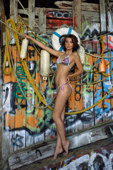 Swimsuit model posing sexy in front of graffiti background