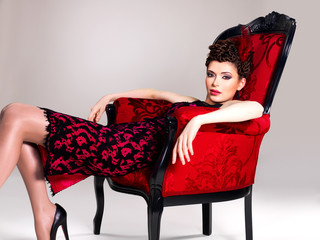 Woman with fashion hairstyle and red armchair Wall mural