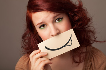 Pretty young girl holding white card with smile drawing