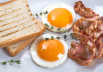 Close-up of fried eggs, bacon and toasts