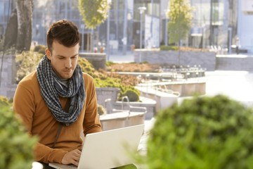 Young man using laptop computer outdoors