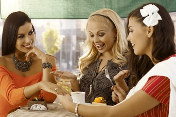 Young woman showing engagement ring to friends