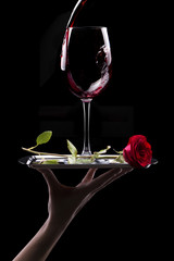 glass of red wine and rose on black