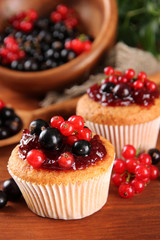 Tasty muffins with berries on wooden table