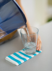 Closeup on housewife pouring water into glass
