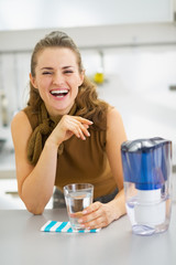 Happy young housewife drinking water from water filter pitcher