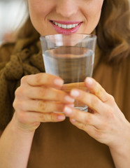 Closeup on woman drinking water in kitchen