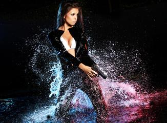 beautiful sexy girl holding gun in water. smoke background