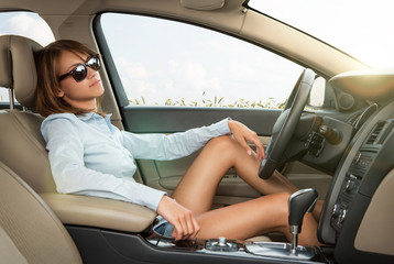 Young girl relaxing in the brand new luxury car
