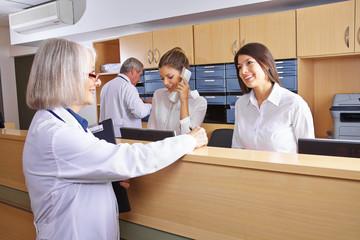 Ärztin mit Empfangsdame an Rezeption