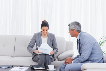 Stressed businesswoman holding documents and businessman trying