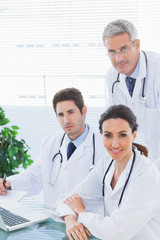 Team of doctors working together looking at camera