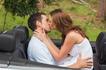 Beautiful couple kissing in back seat