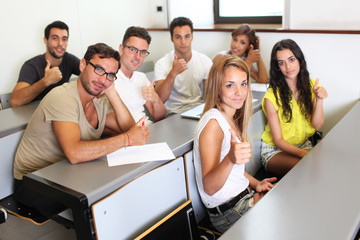 Students holding thumbs up in the university
