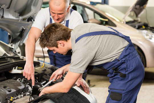 Caucasian car mechanics working together