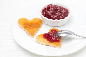 toast in the shape of hearts and berry jam on the plate