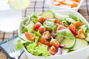 fresh green salad with lettuce, cucumber, tomato and red onion.