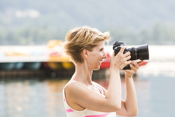 Young woman W34 on vacation takes a picture with her SLR