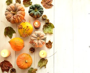Pumpkins with candles on white wood background