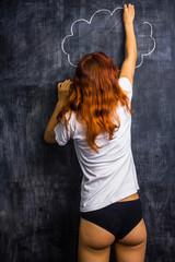 Redhead woman in underwear drawing on a blackboard
