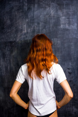 Redhead woman by blank blackboard