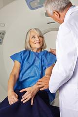 Arzt redet mit Seniorin vor MRT