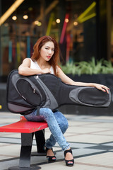 Young beautiful woman posing outdoor with her guitar gig bag