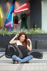 Young beautiful woman posing outdoor with her guitar gig bag