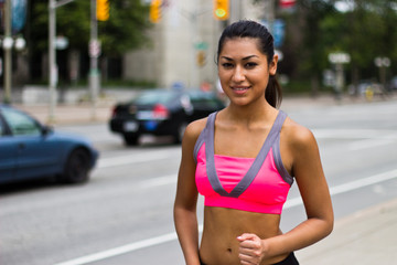 Fit young woman running on a busy city street