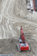 bird's eye fiew of a red digger in sand on a construction area