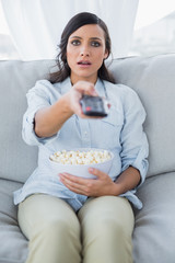 Surprised pretty brunette watching tv and eating pop corn