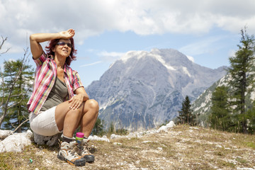 Happy smiling woman hiker resting, sitting high in the mountain