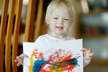 Little toddler girl displaying her picture