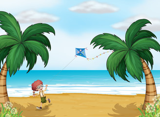 A young boy playing with his kite at the beach