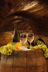 Fototapete - Vine cellar with glasses of white vine against barrels