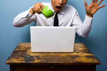 Clumbsy businessman spilling coffee on his laptop computer