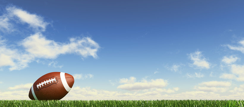 American football ball, on the grass, with fluffy couds sky in t