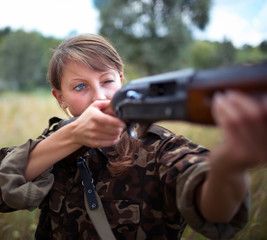 Girl with a gun aiming at a target
