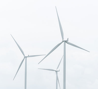 wind turbine in wind farm against cloudy sky