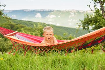 Happy child lying in hammock