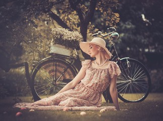 Beautiful dreaming blond retro woman with bicycle
