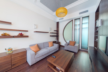 Contemporary room with sofa, an armchair and wooden table