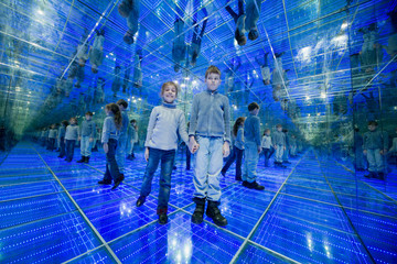 Boy and girl standing in mirrored room with lights