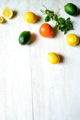 Citrus fruits with mint leaves on white wood background