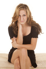 Woman black dress sit facing serious cross legs