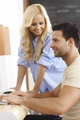 Young couple using computer at home